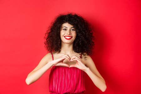 Valentines day. Romantic girl with curly hairstyle in evening dress, smiling and showing heart sign, say I love you on lovers holiday, standing over red background