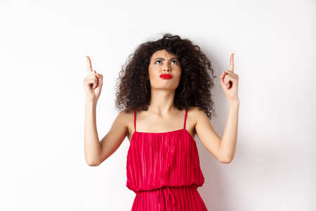 Angry and grumpy woman with curly hair, wearing red dress, frowning and looking up disappointed, standing over white background