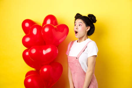 Valentines day and relationship concept. Fashion girl looking amazed, gasping and say wow, staring left while standing near red hearts balloons, surprise from lover, yellow background
