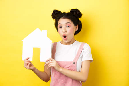 Real estate and family concept. Excited asian teen girl showing paper house cutout and gasping amazed, standing on yellow background