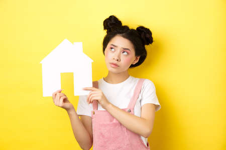 Real estate and family concept. Thoughtful asian girl dream of house, showing paper home cutout and look at upper left corner pensive, yellow background