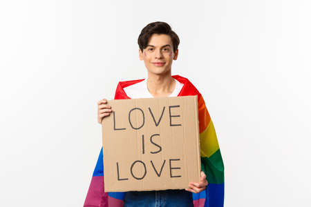 Smiling man activist holding sign love is love for pride parade, wearing Rainbow flag, standing over white background