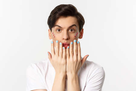 People, lgbtq and beauty concept. Beautiful gay man showing blue nail polish on fingernails and looking at camera, have manicure, standing over white background Stock Photo