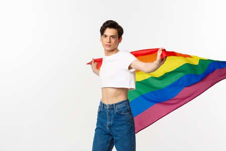 Human rights and lgbtq community concept. Out and proud man waving rainbow flag and looking confident at camera, standing in crop top and jeans against white background