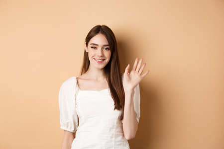 Friendly smiling woman say hello, waiving hand to greet you, standing cheerful on beige background