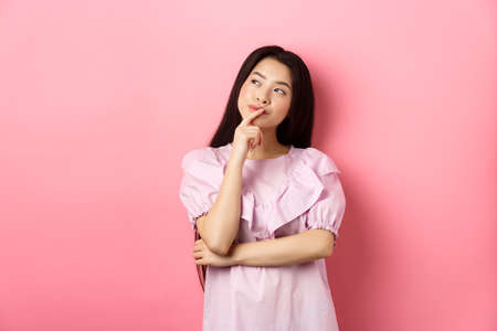Pensive smiling asian girl making choice, looking at upper left corner logo and thinking, having an idea, standing cunning on pink background
