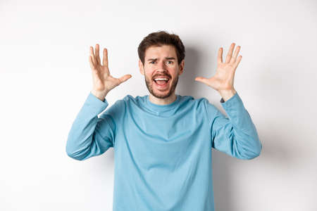 Image of freaked out young man screaming and shaking hands, shouting at camera frustrated or worried, panicking over white background