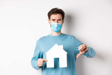 real estate concept. Disappointed young man in medical mask showing paper house cutout and thumb down, dislike broker agency, standing displeased over white background
