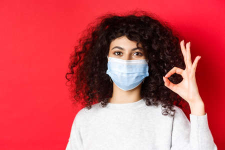 Covid and health concept. Confident young woman in medical mask showing OK gesture in approval, guarantee quality, standing on red background