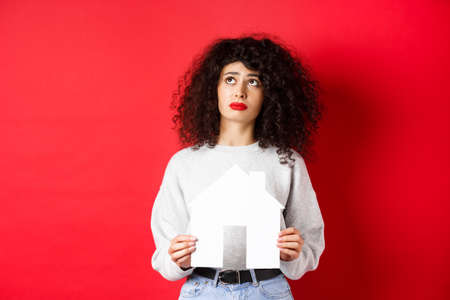 Real estate. Sad woman dreaming of buying apartment, holding paper house cutout and looking up distressed, standing on red background