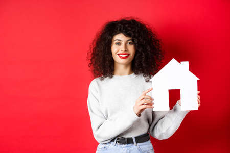 Real estate. Smiling caucasian woman with curly hair and red lips, showing paper house model, searching property, standing on red background