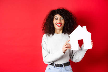 Real estate. Excited smiling woman showing paper house cutout and looking amazed, standing on red background
