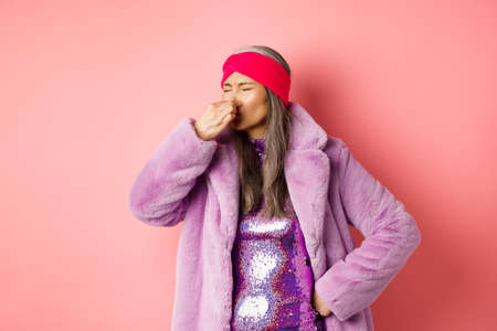Portrait of stylish old asian woman in fashionable purple coat and dress, shut nose from bad smell, express disgust and aversion as something sink awfully, standing over pink background