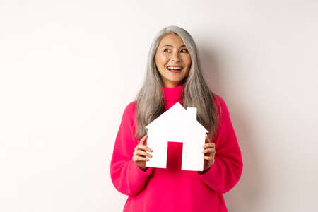 Real estate. Beautiful asian adult woman with grey hair, dreaming about buying property, showing paper house model and looking at upper left corner, white background