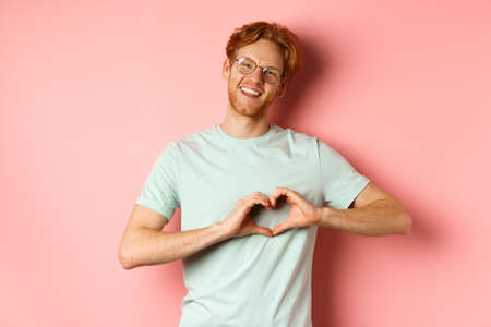 Valentines day concept. Handsome redhead man in glasses, showing heart sign and say I love you, standing over pink background