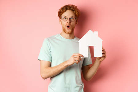 Real estate. Surprised young man with red hair and beard, wearing glasses and t-shirt, showing paper house cutout and looking impressed, saying wow, standing over pink background