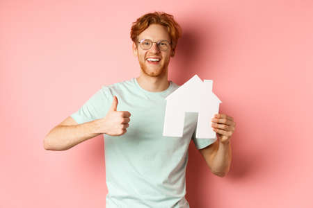 Real estate. Cheerful man in glasses and t-shirt recommending broker agency, showing paper house cutout and thumbs-up, standing over pink background