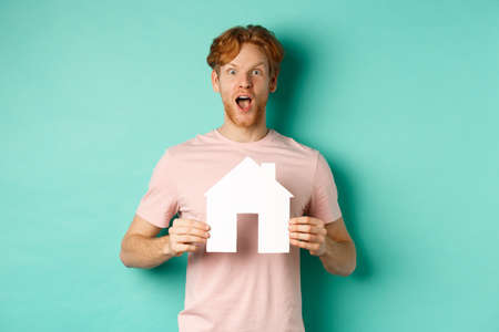Real estate concept. Excited redhead guy with beard, showing paper house cutout and gasping in awe, staring fascinated at camera, standing over mint background