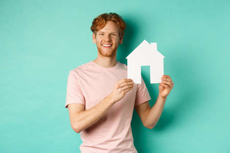 Real estate concept. Young man with red hair, wearing t-shirt, showing paper house cutout and smiling happy, standing over mint background