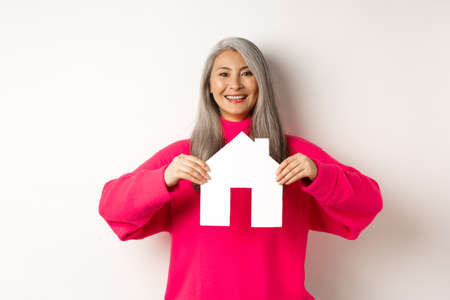 Real estate. Beautiful asian grandmother showing paper house and smiling happy, standing in pink sweater over white background