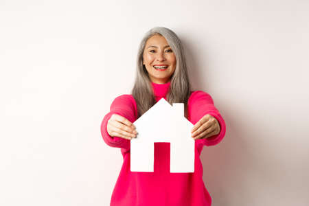 Real estate. Happy korean middle-aged woman with grey hair, showing paper house model and smiling, standing in pink sweater over white background