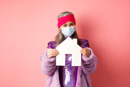 Covid-19 and real estate concept. Senior asian woman in stylish outfit and medical mask showing paper house model, searching apartment, standing over pink background