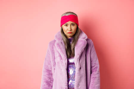 Sad and gloomy stylish asian senior woman looking upset at camera, sulking and feeling distressed, standing in purple faux fur coat against pink background