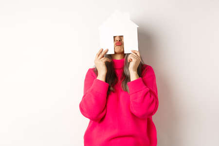 Real estate. Funny asian middle-aged woman hiding face behind paper house model and showing puckered lips, having fun, standing over white background