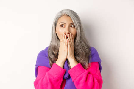 Close-up of shocked asian middle-aged woman with grey hair, gasping and covering mouth startled, looking left, realising something, white background