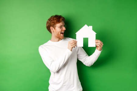 Real estate. Cheerful caucasian man with red hair, looking at paper house cutout and smiling amazed, buying property, standing over green background