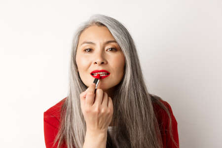 Beauty and fashion concept. Stylish asian mature woman with grey hair, looking in mirror and apply red lipstick, standing over white background