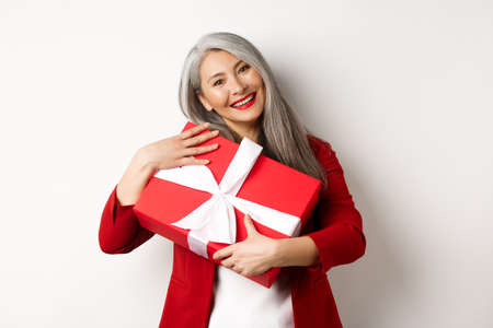 Happy asian grandmother hugging red gift box and smiling grateful, thanking for present, standing over white background