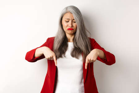 Sad and gloomy asian senior woman in red blazer sulking, pointing fingers down and looking upset, standing over white background Stock Photo