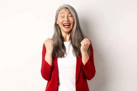 Relieved asian senior businesswoman making fist pump, saying yes and smiling satisfied, triumphing and winning, standing over white background