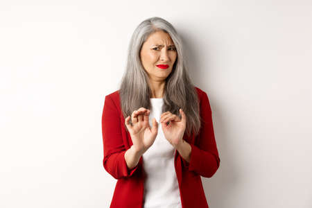 Disgusted asian businesswoman with grey hair, wearing red blazer and makeup, rejecting something disgusting, showing stop sign, white background