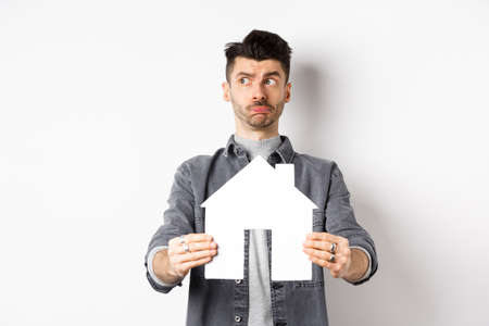 Real estate and insurance concept. Indecisive guy look aside pensive and showing paper house cutout, thinking of buying property, standing against white background