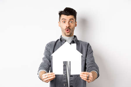 Real estate and insurance concept. Excited man showing paper house cutout and say wow, checking out apartment or property, standing amazed on white background