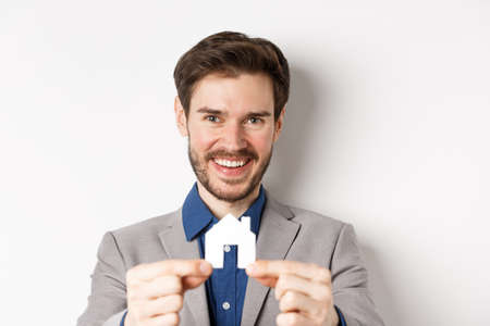 Real estate and insurance concept. Handsome man in suit smiling, showing small paper house cutout, standing on white background