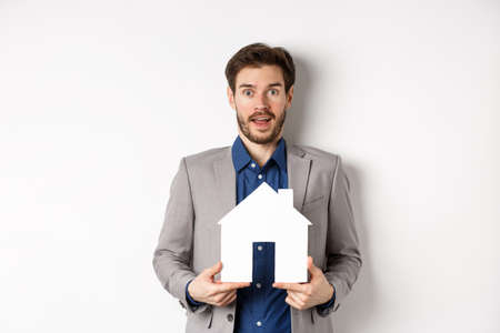 Real estate. Excited business man in suit holding paper house cutout and looking amazed at camera, buying apartment, white background