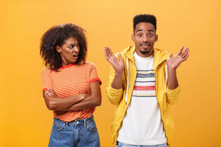 Jeez man what your problem. Offended displeased african american. stylish and attractive girlfriend looking at boyfriend acting cool pretending he uninvolved shrugging with sorry look and smiling.