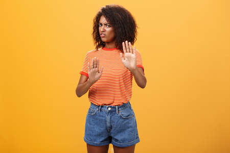 No I refuse. Intense suspicious and displeased smart african-american female rejecting bad offer pulling raised palms turning away with aversion and dissatisfied look against orange background