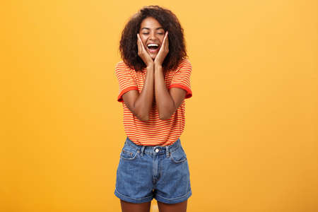 Woman happy and delighted with great result after curing acne with skincare products touching cheeks smiling happily with closed eyes feeling pleased and amused over orange background