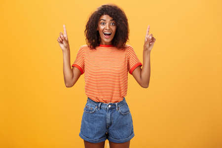 Charmed and impressed african american stylish woman seeing incredible and awesome item on sale raising hands and pointing up with broad grin being excited of new purchase over orange wall