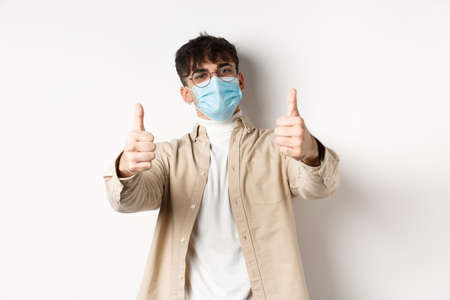 Health and real people concept. Smiling guy in medical mask showing thumbs up, wearing glasses, standing on white background