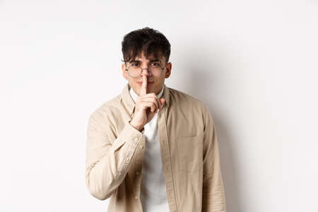 Cheerful handsome man in glasses share a secret, making surprise, lean at camera with hush gesture and gentle smile, telling to be quiet, show taboo sign, white background