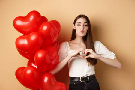 Lovely girlfriend pucker lips and waiting for romantic kiss, showing heart gesture to say I love you, look at lover, standing near Valentines day balloons and beige background
