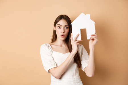 Real estate. Excited young woman showing house cutout and looking at camera, renting property, standing on beige background