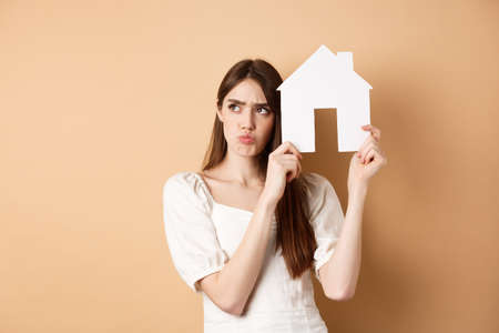 Real estate. Upset young woman showing paper house cutout and frowning sad, looking aside thoughtful, thinking of buying apartment, standing on beige background