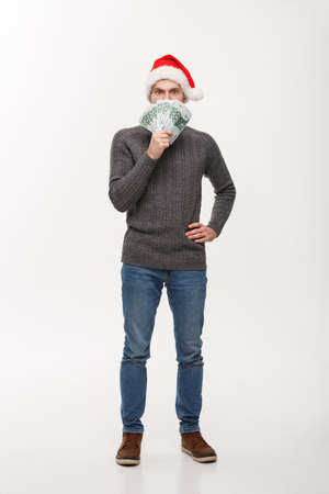Holiday Concept - young beard man holding money in front over white background