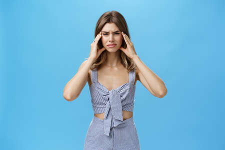 Woman having mental breakdown about to cry having uneasy troublesome situation holding hands on temples frowning making miserable expression suffering from migraine or headache over blue wall